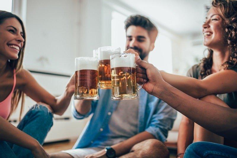 Freunde-essen-Popcorn-und-trinken-Bier-zu-Hause