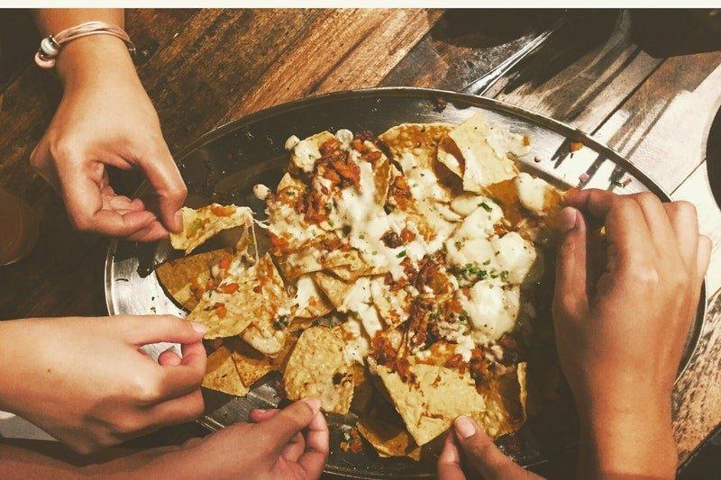 Nahaufnahme-von-Menschen-die-Nachos-Chips-essen
