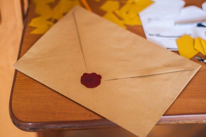 Partyeinladung-innerhalb-des-braunen-Papierumschlags-auf-dem-Tisch