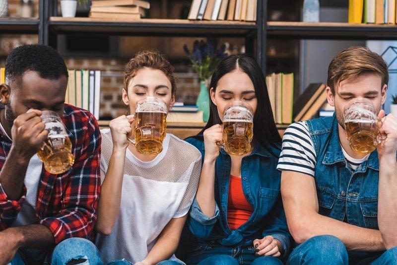 junge-Freunde-sitzen-zusammen-und-trinken-Bier
