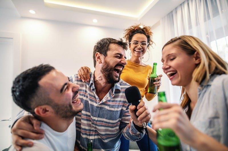 Gruppe von Freunden, die Bier trinken und singen, lustige Partyspiele für Erwachsene spielen