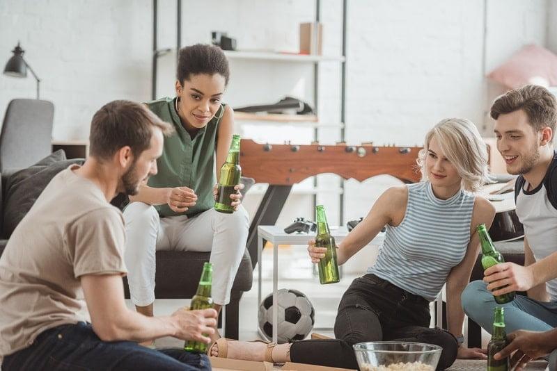 Freunde die mit Bierflaschen jubeln