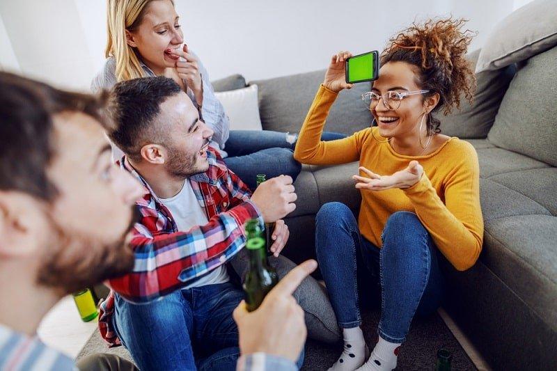 Freunde spielen Scharaden mit Smartphone