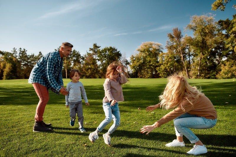 Eltern spielen mit ihren beiden Kindern Fangen