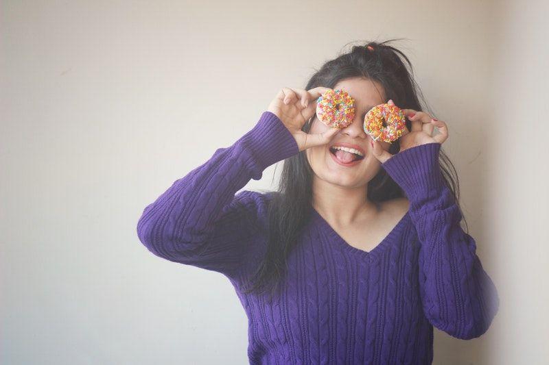 Frau bedeckt ihre Augen mit Donuts