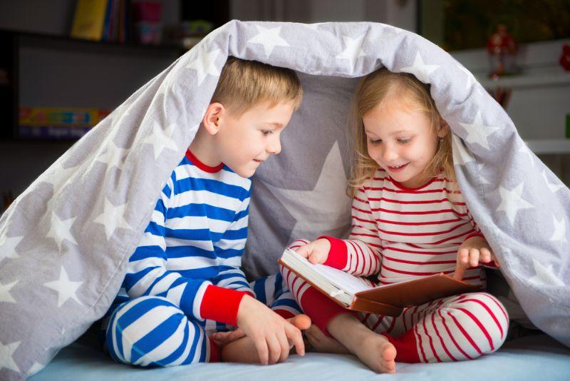 Geschwister lesen Buch unter dem Deckmantel