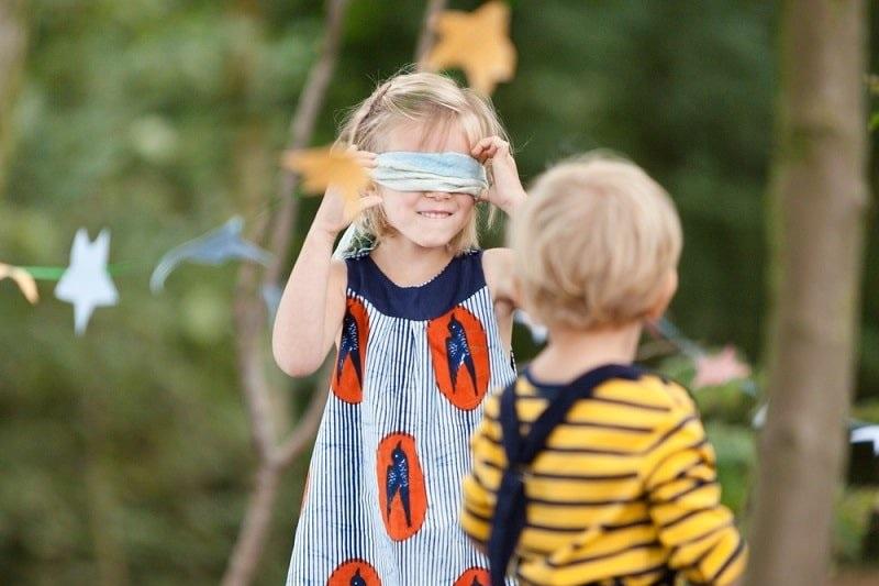 Kinder-spielen-draußen-mit-einer-Augenbinde