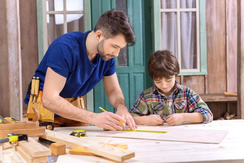 Vater und Sohn in der Werkstatt arbeiten mit Holz