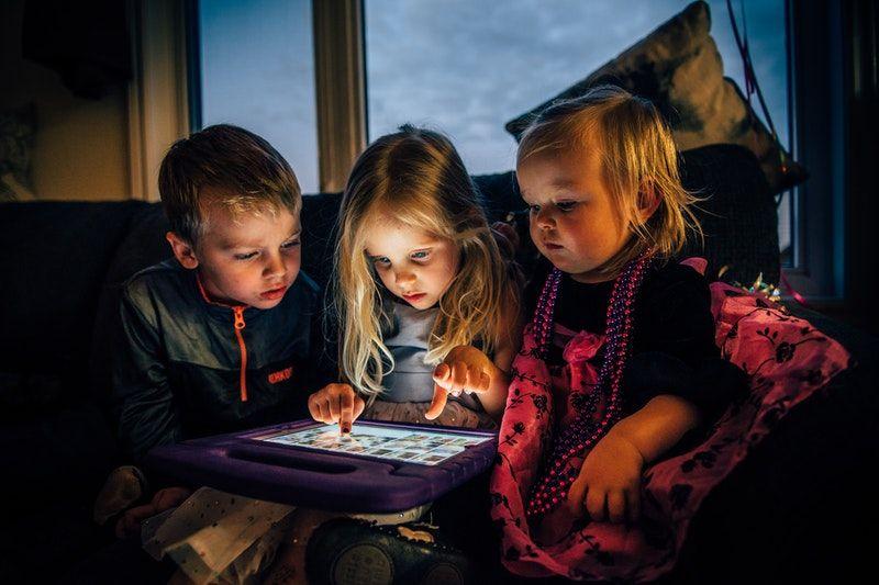 drei Kinder schauen auf ein Tablet