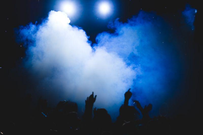 Menschen stehen in einem dunklen Raum mit Hintergrundbeleuchtung und Nebel