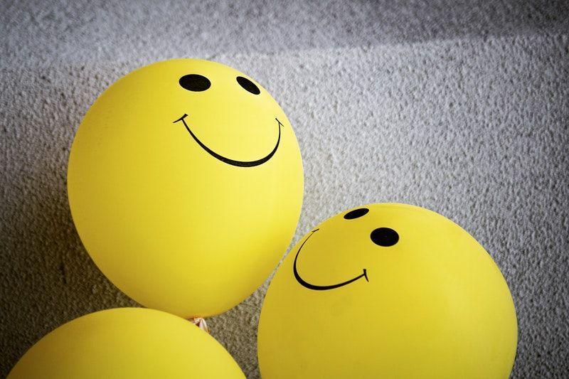 gelber Smiley-Emoji-Ballon auf grauer Oberfläche