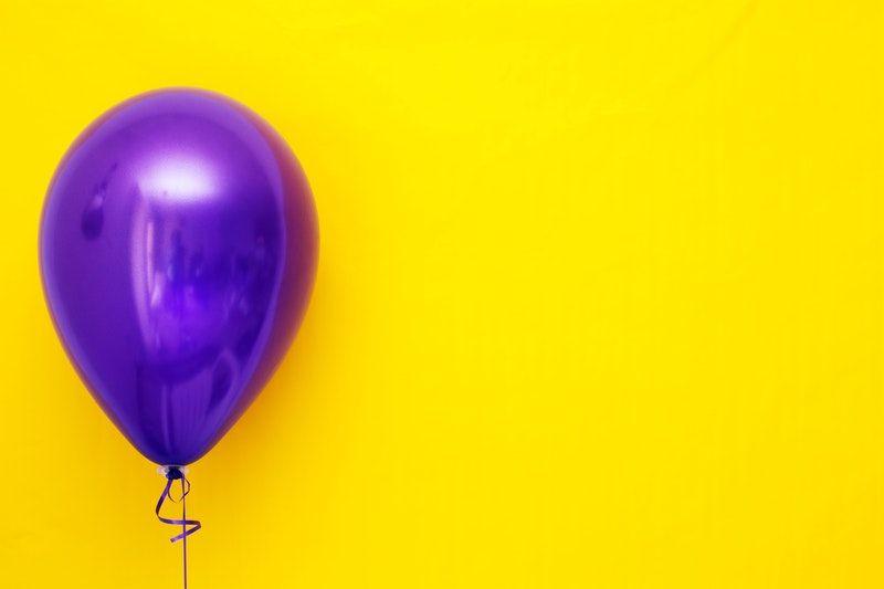 lila Ballon auf einem gelben Hintergrund