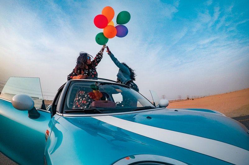 zwei Frauen, die verschiedene Farbballon viel im Cabrio Auto halten