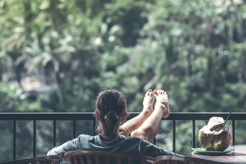 Frau sitzt auf dem Balkon mit den Füßen in der Luft