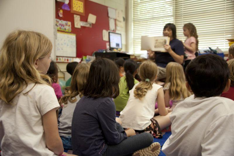 Grundschullehrer mit Kindern auf dem Boden sitzen