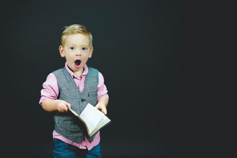 kleiner Junge mit einem schockierten Gesichtsausdruck auf schwarzem Hintergrund