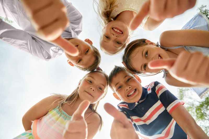 Kinder zeigen Daumen nach oben im Kreis