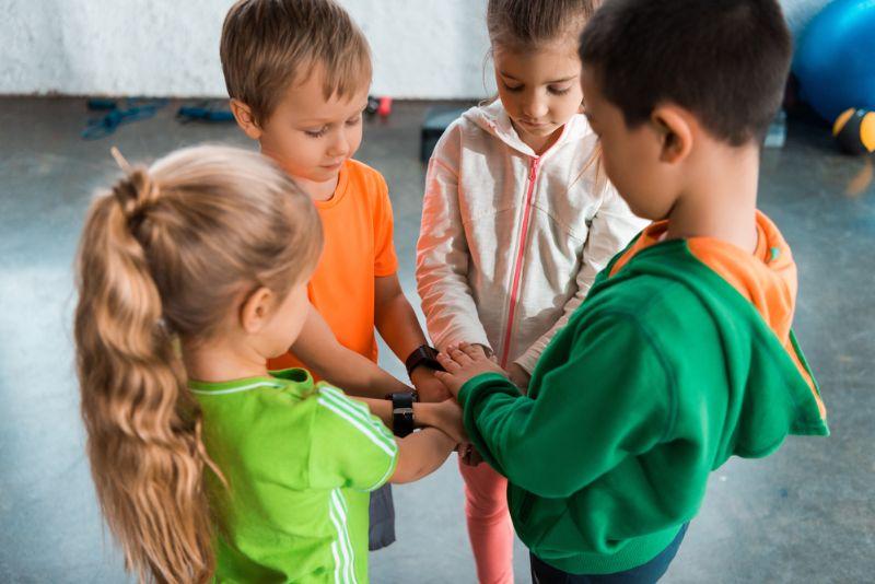 Gruppe von Kindern, die Spiele spielen, während sie in einem Kreis stehen
