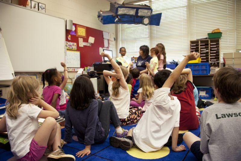 Grundschullehrer mit Kindern, die auf dem Boden sitzen und sich strecken