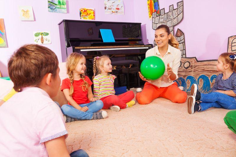Lehrer mit Grundschulkindern, die Spiele spielen