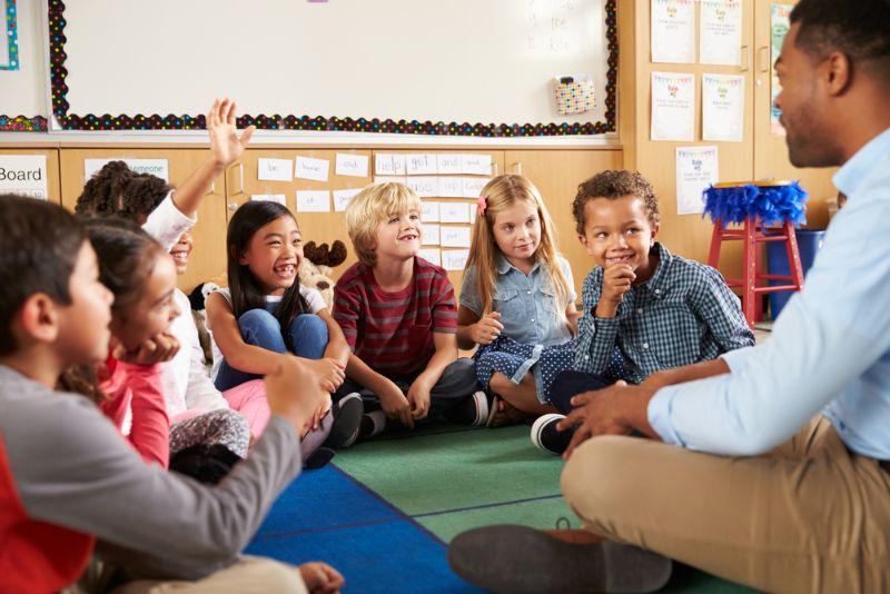kleine Kinder sitzen mit Lehrer auf dem Boden und lachen