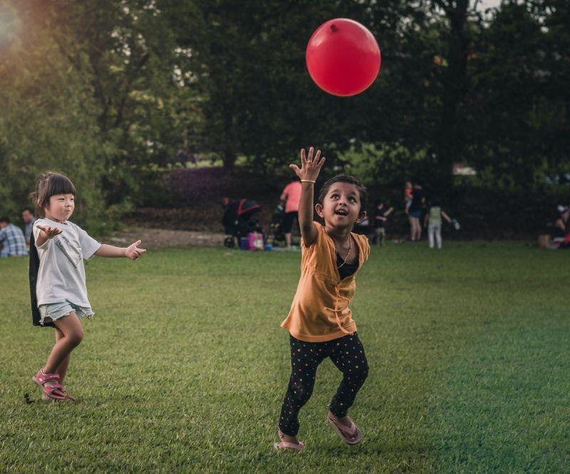 zwei Kinder laufen und spielen mit Ballon