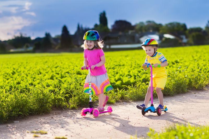 Kinder-die-Roller-am-sonnigen-Sommertag-fahren