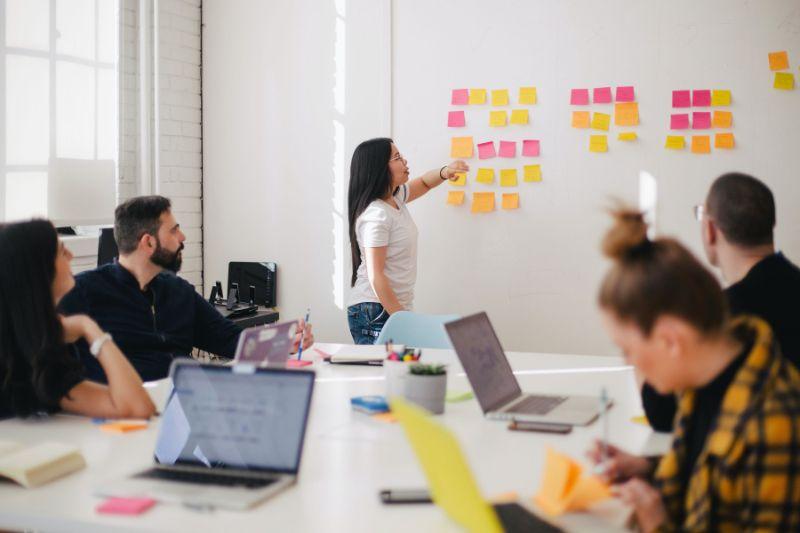 Frau Präsentiert Ideen Für Teambuilding Auf Aufklebern In Verschiedenen Farben