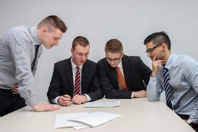 Vier Geschäftsleute Die Auf Ein Papier Hinunterblicken