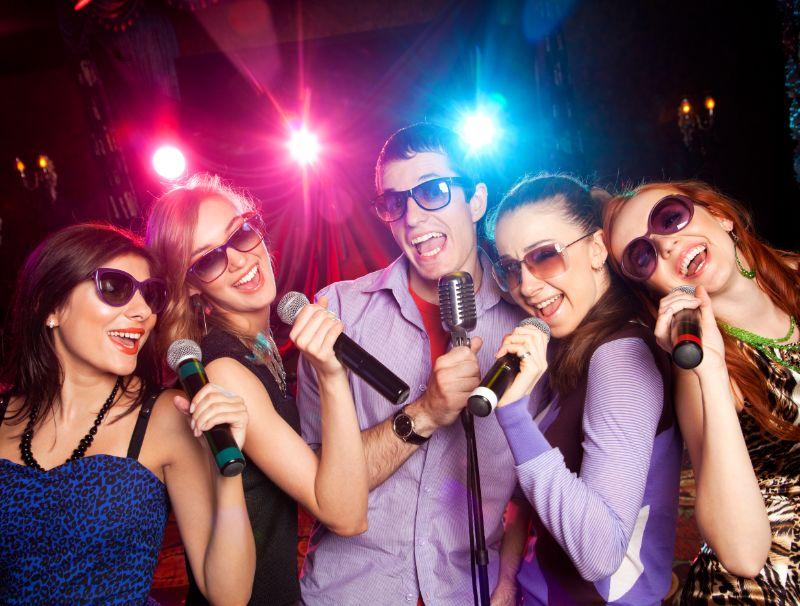 Gruppe-junger-Leute-die-auf-der-Karaoke-Party-ins-Mikrofon-singen.