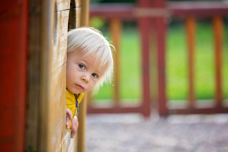 Blondes-kleines-Kleinkindkind-in-gelber-Jacke-das-auf-dem-Spielplatz-spielt