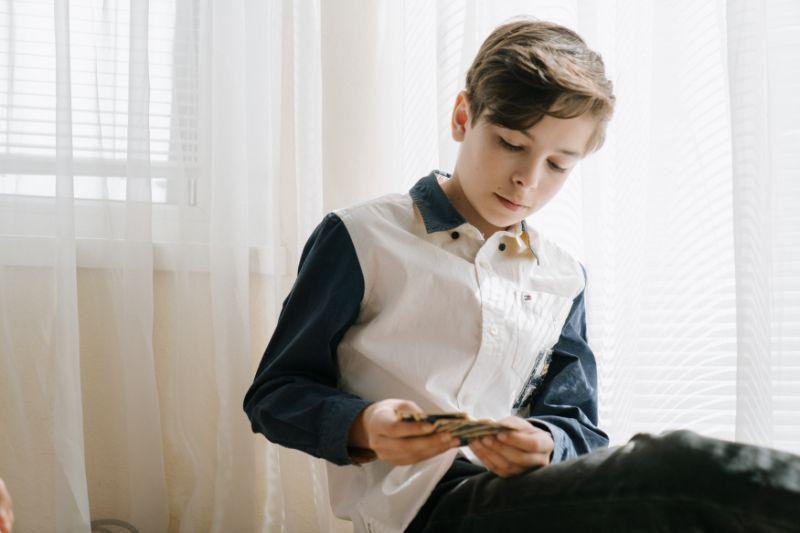 Junge-halt-Spielkarten-in-Handen