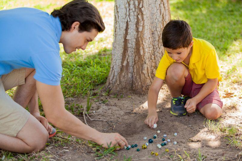 Vater-und-Sohn-spielen-Murmeln