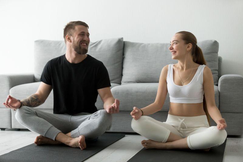 Junges-gluckliches-Paar-das-Spas-hat-Yoga-zusammen-zu-Hause-zu-tun