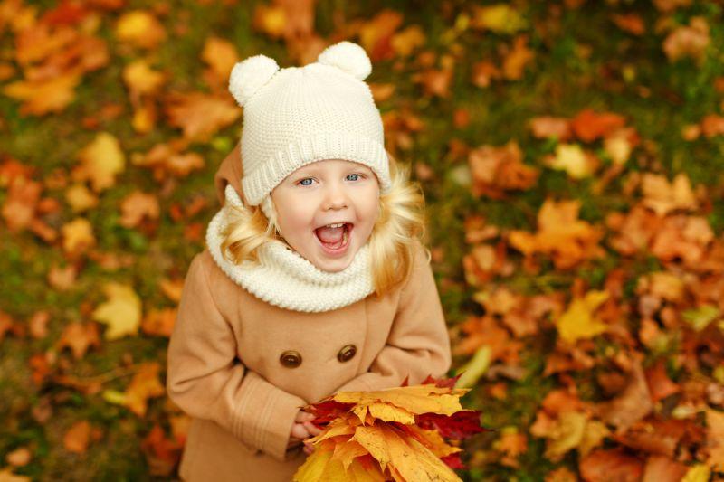 Kleines-hubsches-Madchen-in-einem-beigen-Mantel-lacht-im-Herbst-in-einem-Park