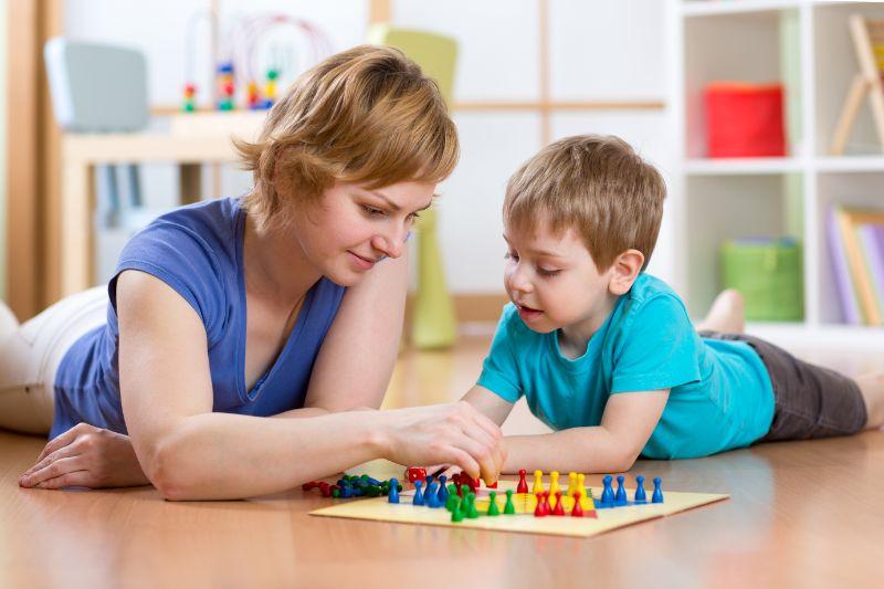Mutter-und-Sohn-spielen-Brettspiel-Mensch-argere-Dich-nicht-zu-Hause-auf-dem-Boden