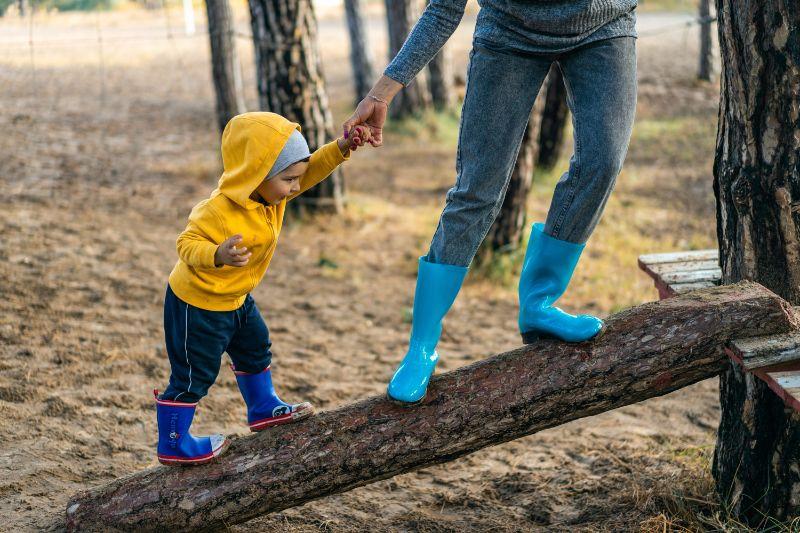 ein-kleiner-Junge-in-einer-gelben-Jacke-der-mit-Hilfe-eines-Elternteils-ein-Hindernis-uberwindet