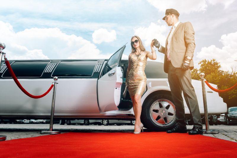 Fahrer-hilft-VIP-Frau-oder-Star-aus-der-Limousine-auf-rotem-Teppich