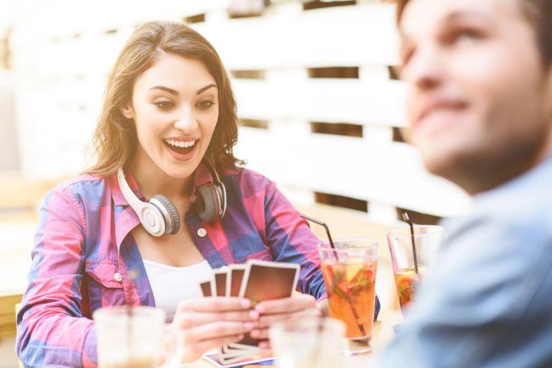 Freunde-die-Kartenspiel-spielen-wahrend-sie-im-Strasencafe-sitzen