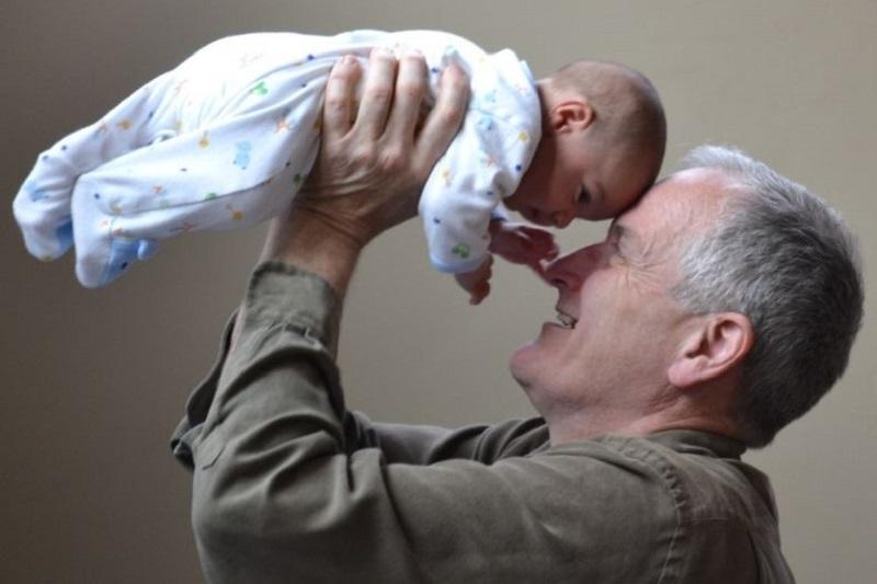 Grosvater-spielt-mit-seinem-neugeborenen-Enkelkind