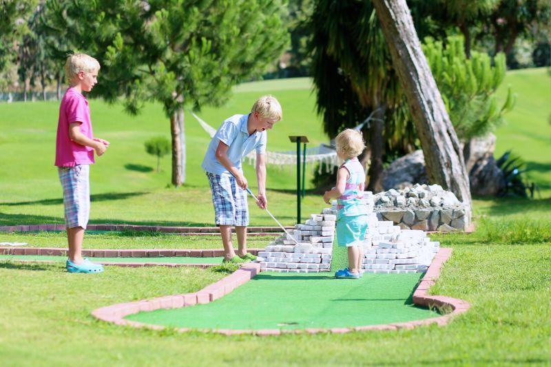 Gruppe-von-Kindern-die-im-Freien-Minigolf-spielen
