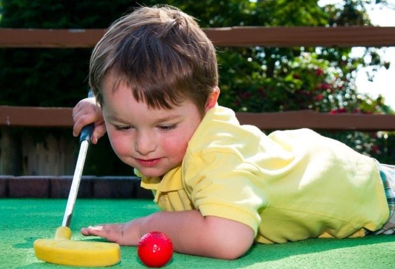 Junge-spielt-Minigolf-auf-Putt-Putt-Platz.