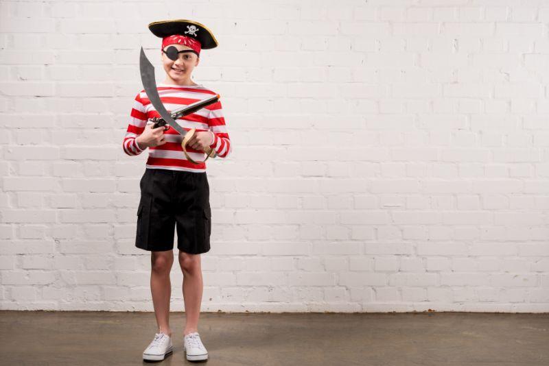 Kleiner-lachelnder-Junge-mit-Spielzeugmesser-und-Pistole-im-Piratenkostum