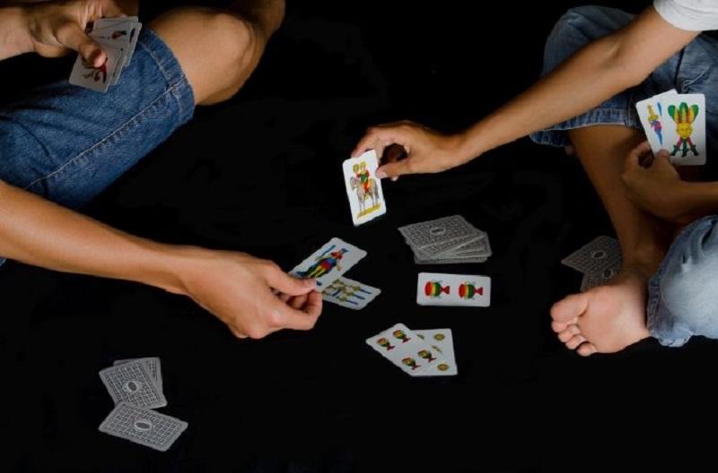 Zwei-Jungen-die-nachts-Karten-auf-schwarzem-Boden-spielen-1