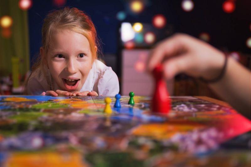 Brettspielkonzept-Ihr-Zug.-Kleines-Madchen-beobachtete-das-Spiel-und-schockierte-von-der-Aktion.