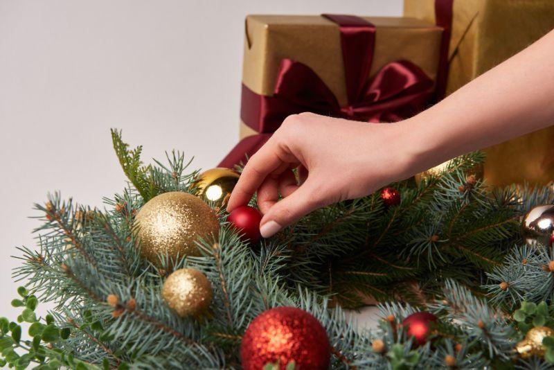 Frau-die-Weihnachtstannenkranz-mit-Kugeln
