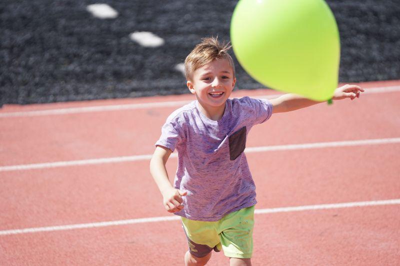 Kind-lachelt-und-lauft-mit-einem-Ballon