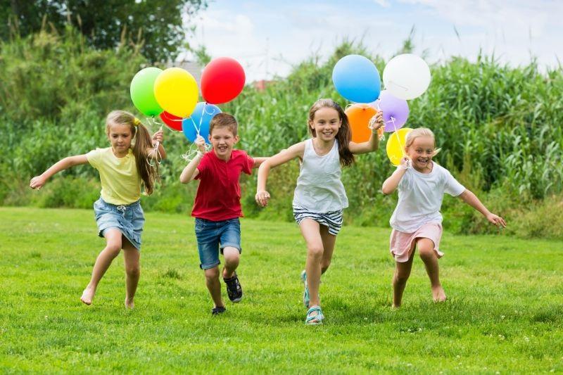 Kinder-laufen-mit-bunten-Luftballons