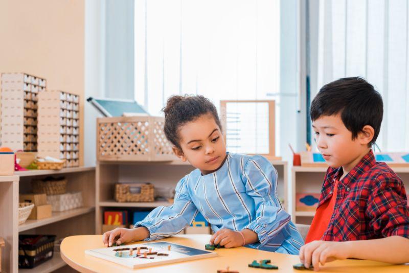 Kinder-spielen-Brettspiel-am-Tisch-in-der-Montessori-Klasse