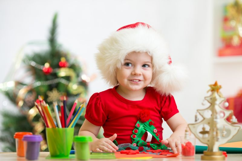 Kindermadchen-in-der-Weihnachtsmutze-die-Weihnachtsdekoration-von-Plastilin-macht